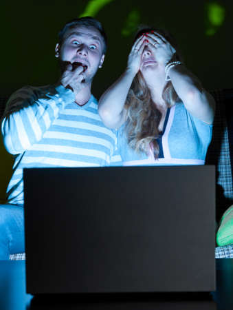 couple is watching scary movie indoors at night photo