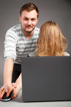 handsome man is helping weird woman with hair on face to work with laptop photo