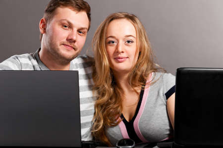 man and woman is sitting together on gray background with laptops photo