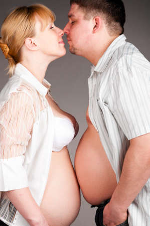 man and pregnant woman is standing face to face and showing their bellies and kissing, side view photo