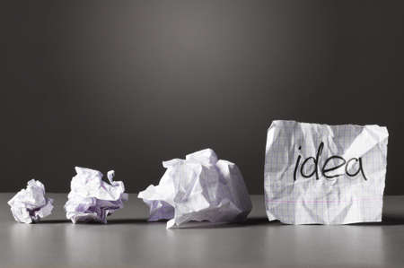evolution: hoja de papel con la idea de palabra y bolitas de periódicos en la tabla. Foto de archivo