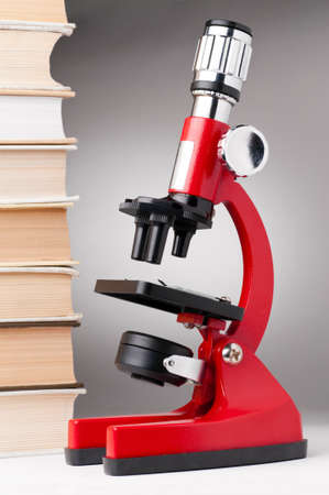 books and red microscope, scientific or educational concept photo