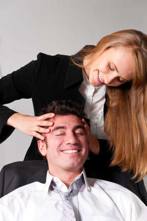 young businesswoman is making head massage to her teammate photo