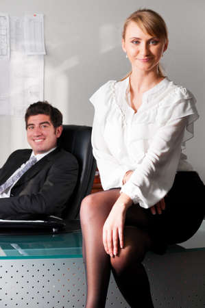 businesswoman is sitting on table at office with her boss in chair photo