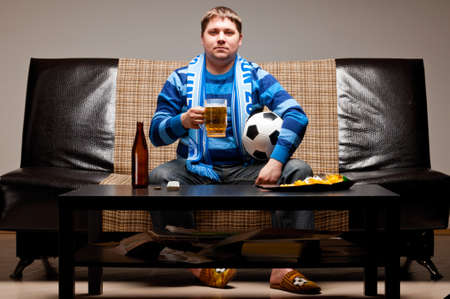 soccer fan is sitting on sofa with beer at home photo