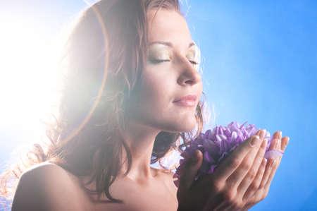 hermosa mujer con grandes flores sobre fondo azul