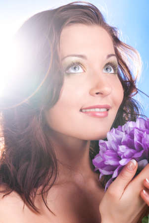 beautiful woman with flower is looking at camera on blue background photo