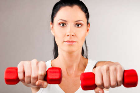 woman is holding barbells photo