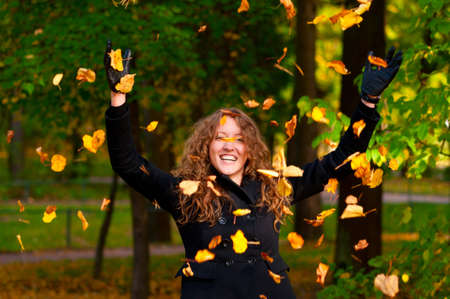 throwing dry autumn leaves in park photo