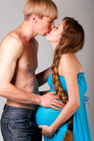 kissing pregnant belly: man is kissing pregnant woman