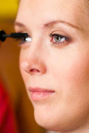 woman is applying mascara photo
