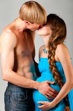 man is kissing pregnant woman photo