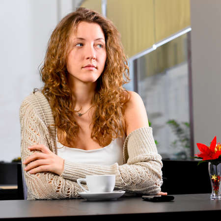 young woman is sitting at cafe photo