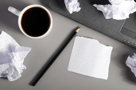 crumpled sheet: business creativity concept. Laptop, sheets of paper and crumpled wads on table.