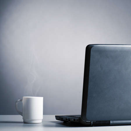 laptop and cup of hot evaporating coffee on table, blue toned Stock Photo - 13642203