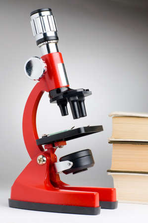 optical equipment: books and microscope, scientific or educational concept Stock Photo
