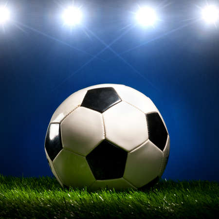 soccer ball is lying on grass on field at stadium photo