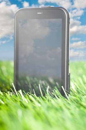 touch screen phone is standing in grass outdoors photo