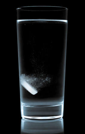 tablet in water glass isolated on black photo