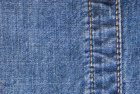 Highly detailed jeans texture with vertical seam. Can be used as a background. photo