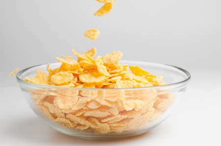 cornflakes: closeup of a bowl with pouring cereal flakes Stock Photo