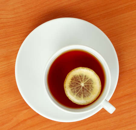 above water: tea cup with lemon on wooden table from above