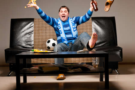 man watching tv: soccer fan on sofa