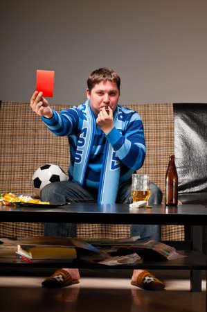 watching football: soccer fan on sofa