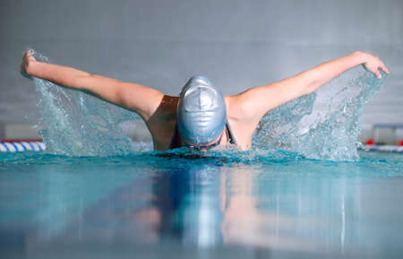swimming competition: woman swims using the butterfly stroke in indoor pool