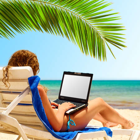 woman sitting with laptop: surfing on the beach