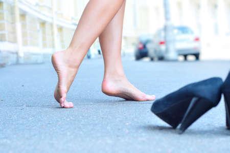 woman naked body: female bare feet dancing on summer street