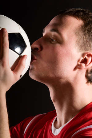 soccer player is kissing the ball photo