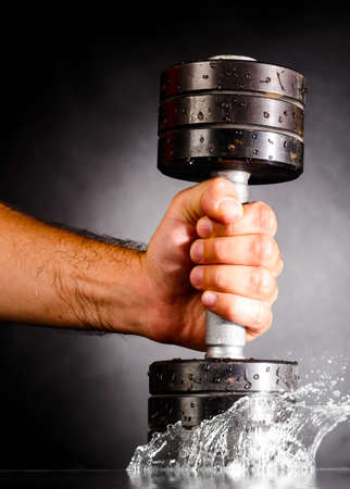 metal barbell splashes in water photo
