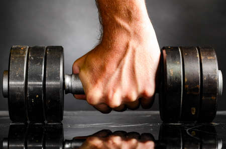 heavy lifting: male hand is holding metal barbell