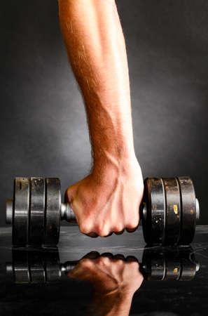 hombre fuerte: mano masculina sostiene barra de metal Foto de archivo