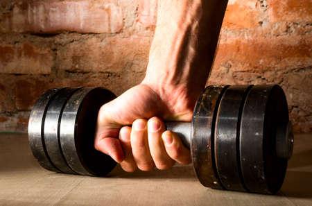 mannelijke hand houdt metalen halter