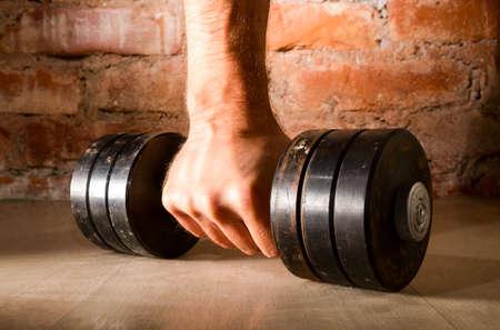 lifting: mannelijke hand houdt metalen halter