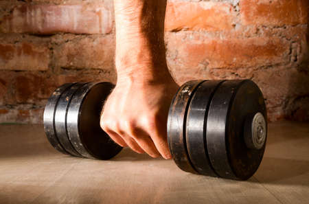 levantando pesas: mano masculina sostiene barra de metal Foto de archivo