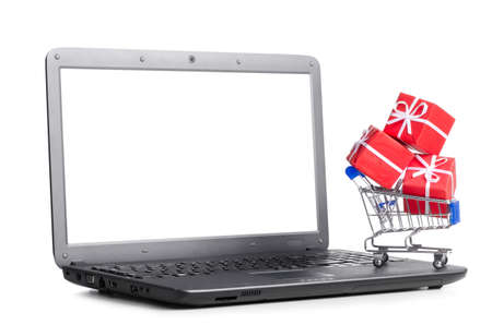 red gift boxes in shopping cart on a laptop, cut out from white photo
