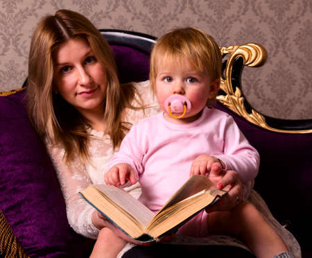 mother and her baby are reading photo