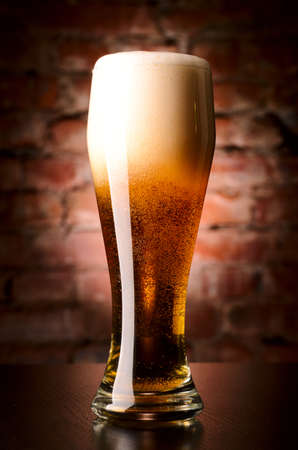 glass of lager on table against brick wall Stock Photo