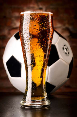 glass of lager with soccer ball on table against brick wall photo