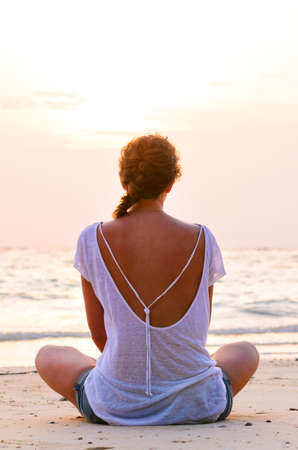 woman is sitting on beach at sunrise photo