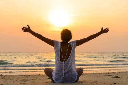 vrouw zit op het strand bij zonsopgang Stockfoto