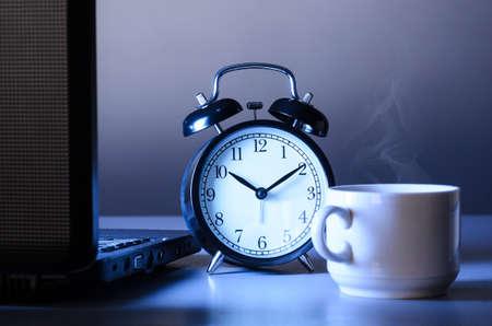 's nachts werken, laptop en kop warme verdampende koffie op tafel