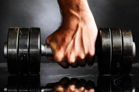 gym floor: male hand is holding metal barbell