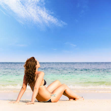 woman is sitting on beach photo