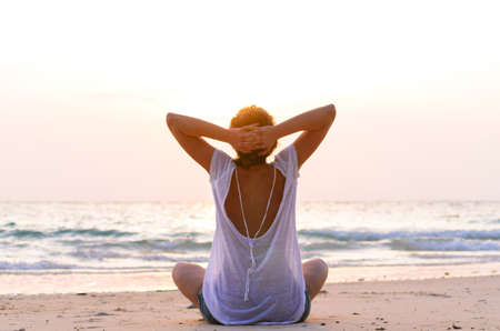 woman from behind: sitting on beach at sunrise