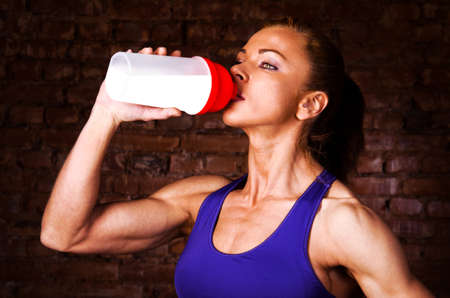 supplements: strong woman is drinking sports nutrition