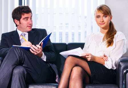 two business persons are sitting and discussing on leather sofa at office Stock Photo - 18705620